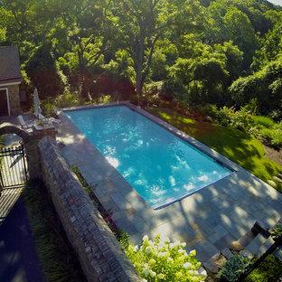 Imagen de piscina tradicional, de tamaño medio, rectangular, en patio lateral, con adoquines de piedra natural