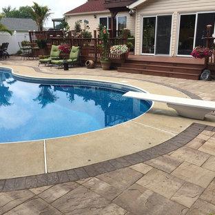Foto de piscina alargada, tradicional, de tamaño medio, tipo riñón, en patio trasero, con adoquines de piedra natural