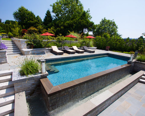 Infinity Pool Designs this is a great example of how big a role landscaping plays in your pool design by adding native plants rock features and a waterfall this infinity pool Elegant Backyard Rectangular Infinity Pool Photo In Vancouver