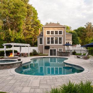 Elegant backyard kidney-shaped hot tub photo in Boston