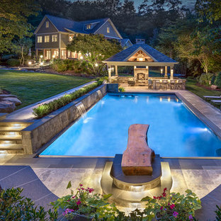 This is an example of a classic back rectangular swimming pool in Richmond with a water feature and natural stone paving.