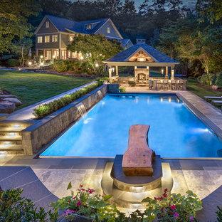 Foto de piscina con fuente tradicional, rectangular, en patio trasero, con adoquines de piedra natural