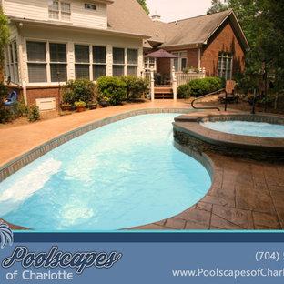 """Immagine di una grande piscina chic a """"C"""" dietro casa con una vasca idromassaggio e cemento stampato"""