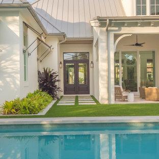 Esempio di una grande piscina monocorsia country rettangolare dietro casa con una vasca idromassaggio e pavimentazioni in pietra naturale
