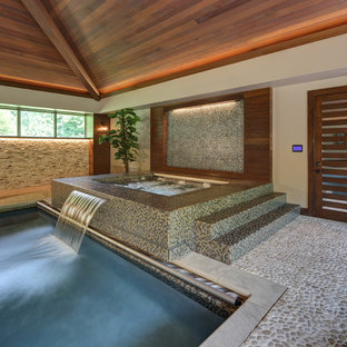 Design ideas for a contemporary rectangular pool in Cleveland with a water feature and decking.