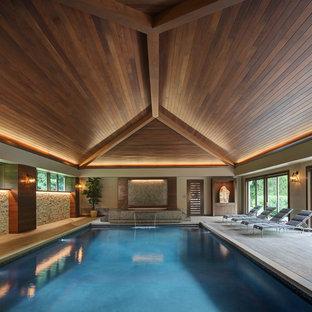 Esempio di una piscina coperta design rettangolare con fontane e pedane