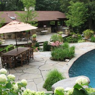 Modelo de piscinas y jacuzzis alargados, de estilo americano, de tamaño medio, tipo riñón, en patio trasero, con adoquines de piedra natural