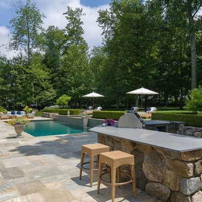 Mid-sized transitional backyard stone and rectangular lap hot tub photo in New York