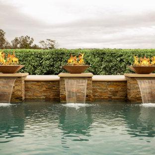 Ejemplo de piscina con fuente alargada, tradicional renovada, de tamaño medio, rectangular, en patio trasero, con adoquines de piedra natural