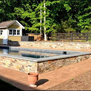 Ejemplo de casa de la piscina y piscina elevada, clásica renovada, de tamaño medio, rectangular, en patio trasero, con adoquines de hormigón