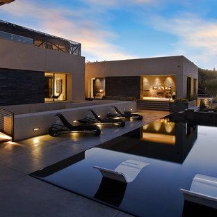 Immagine di una piscina a sfioro infinito design rettangolare dietro casa