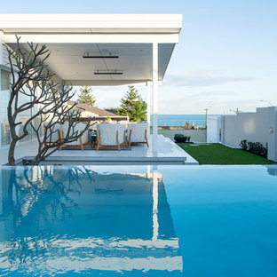 This is an example of a mid-sized beach style backyard rectangular infinity pool in Perth.