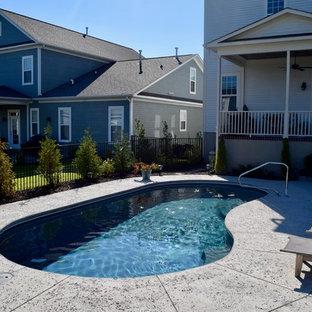 Ejemplo de piscina alargada, minimalista, de tamaño medio, tipo riñón, en patio trasero, con losas de hormigón