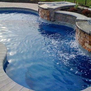 Ejemplo de piscina con fuente actual, de tamaño medio, tipo riñón, en patio trasero, con adoquines de ladrillo