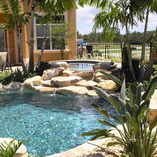 Modelo de piscina con fuente tropical, grande, a medida, en patio trasero, con gravilla