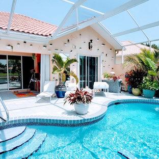 Ejemplo de piscina bohemia, de tamaño medio, tipo riñón, en patio trasero, con losas de hormigón