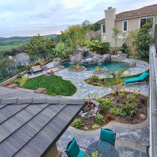 Ejemplo de piscinas y jacuzzis alargados, tropicales, de tamaño medio, tipo riñón, en patio trasero, con adoquines de piedra natural