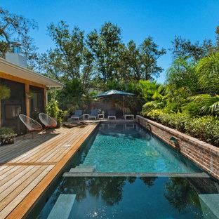 Foto di una piccola piscina tropicale rettangolare nel cortile laterale con pedane