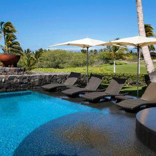 Pool - tropical backyard rectangular infinity pool idea in Hawaii