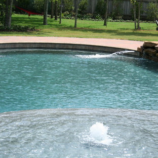 Hot tub - large tropical backyard brick and custom-shaped natural hot tub idea in Austin