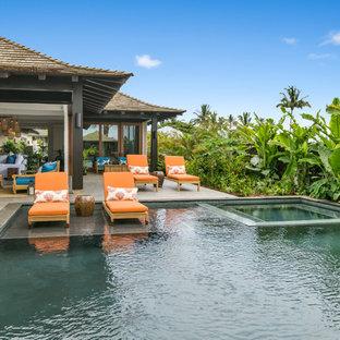 Foto de piscinas y jacuzzis tropicales, de tamaño medio, rectangulares, en patio trasero, con suelo de baldosas