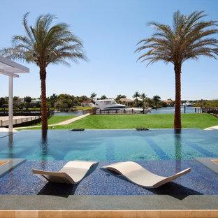 Foto di un'ampia piscina a sfioro infinito tropicale rettangolare dietro casa con piastrelle
