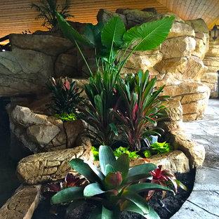 Foto de piscina con fuente alargada, tropical, de tamaño medio, a medida, en patio trasero, con adoquines de piedra natural