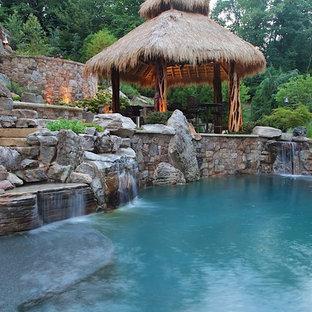 Ejemplo de piscina con fuente tropical, grande, en patio trasero