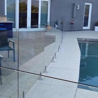 Modelo de piscinas y jacuzzis contemporáneos, de tamaño medio, rectangulares, en patio trasero, con losas de hormigón