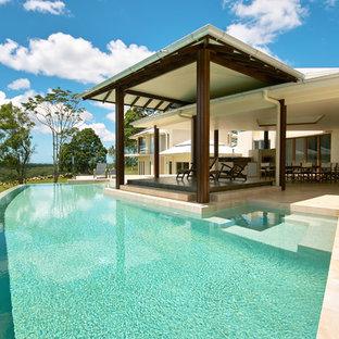 Example of a mid-sized island style backyard custom-shaped infinity pool design in Brisbane