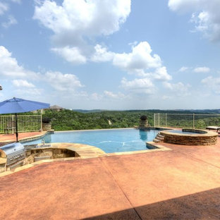 Photo of a large backyard custom-shaped infinity pool in Austin with a hot tub.