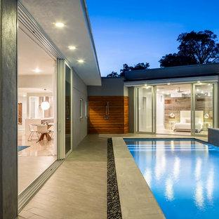 Imagen de piscina con fuente vintage, de tamaño medio, rectangular, en patio trasero, con suelo de baldosas