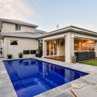 Imagen de piscina alargada, minimalista, de tamaño medio, rectangular, en patio trasero, con adoquines de piedra natural