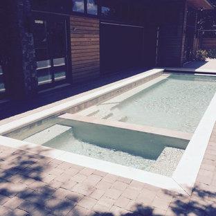 Ejemplo de piscinas y jacuzzis naturales, eclécticos, de tamaño medio, rectangulares, en patio trasero, con adoquines de ladrillo