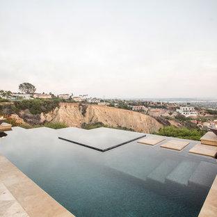 Imagen de piscina infinita, mediterránea, grande, a medida, en patio trasero, con adoquines de piedra natural