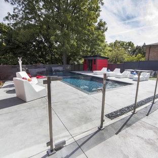 Modelo de casa de la piscina y piscina alargada, moderna, de tamaño medio, rectangular, en patio trasero, con suelo de hormigón estampado