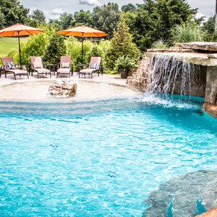 Foto de piscina con fuente natural, exótica, grande, a medida, en patio trasero, con suelo de hormigón estampado