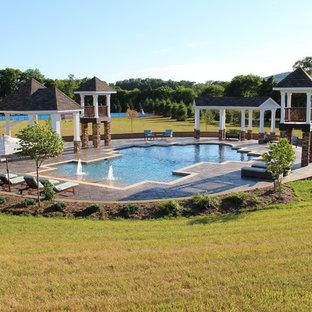 Foto de piscina con fuente natural, tradicional, extra grande, a medida, en patio trasero, con suelo de hormigón estampado
