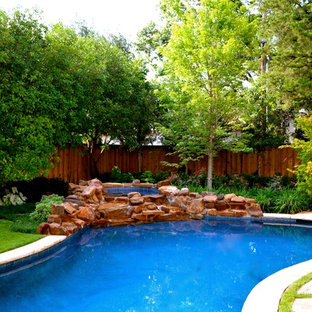 Mid-sized elegant backyard stone and kidney-shaped pool fountain photo in Dallas