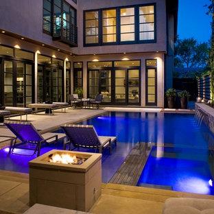 Foto de casa de la piscina y piscina infinita, moderna, de tamaño medio, rectangular, en patio, con entablado