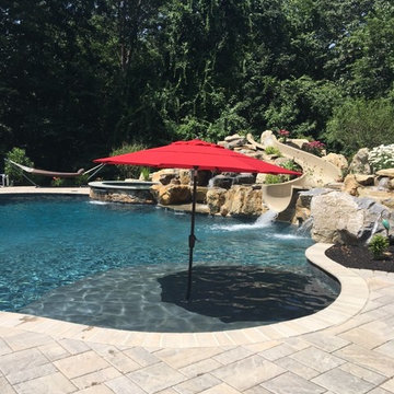 Upper Saucon large custom pool with boulder waterfall, slide, sunshelf, and spa