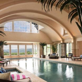 Immagine di una grande piscina coperta monocorsia chic rettangolare con una vasca idromassaggio e piastrelle