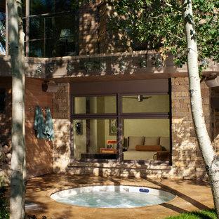 Diseño de piscinas y jacuzzis contemporáneos, grandes, redondeados, en patio trasero, con adoquines de piedra natural