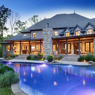 This is an example of a mid-sized arts and crafts backyard custom-shaped natural pool in Nashville with a hot tub and natural stone pavers.