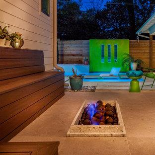 Ejemplo de piscina minimalista, de tamaño medio, en forma de L, en patio trasero, con losas de hormigón