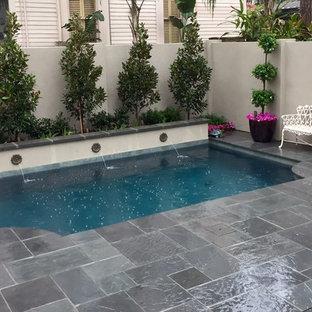 Ejemplo de piscina con fuente alargada, tradicional, de tamaño medio, rectangular, en patio trasero, con adoquines de piedra natural