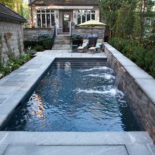 Esempio di una piccola piscina monocorsia tradizionale rettangolare dietro casa con fontane e pavimentazioni in pietra naturale