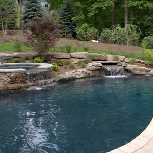 Example of a large mountain style front yard concrete paver and custom-shaped natural hot tub design in New York
