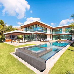 Großer Moderner Pool hinter dem Haus in rechteckiger Form mit Betonplatten in Miami