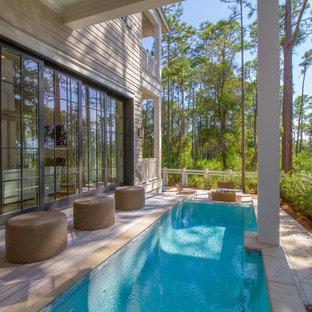 Ispirazione per una piscina stile marino dietro casa con pedane